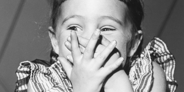 Girl (4-5) giggling, covering mouth, (B&W)