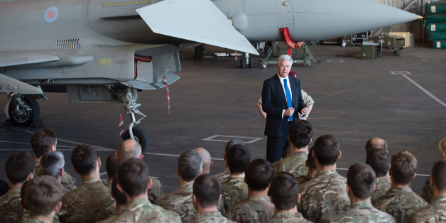 British Defence minister Michael Fallon talks to British pilots and soldiers at RAF Akrotiri, a British air base near the coastal city of Limassol, Cyprus, Saturday, Dec. 5, 2015. British warplanes carried out airstrikes in Syria early Thursday, hours after Parliament voted to authorize air attacks against Islamic State group targets there. Eight more British jets arrived at RAF Akrotiri to join the attacks. (AP Photo/Pavlos Vrionides)