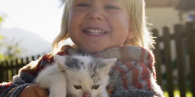 Junge hält Katze