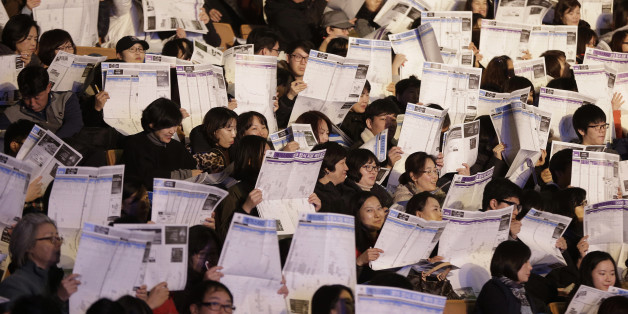 Students and their parents check lists of colleges during a presentation by a private educational academy on how to select the right college for this year's college entrants at Jamsil gymnasium in Seoul, South Korea, Thursday, Dec. 3, 2015. Results of the College Scholastic Aptitude Test came out on Dec. 2, and applicants need to find the colleges they qualify for depending on their test scores. (AP Photo/Ahn Young-joon)
