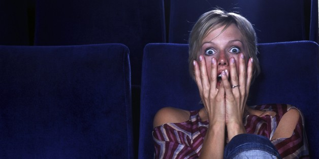 Blond woman in movie theater viewing horror film