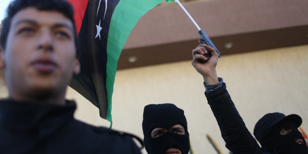 Libyan security forces stand in front of the security headquarters, one showing his weapon with a Libyan flag, in the western city of Sabratha, Libya, Saturday, Feb. 20, 2016. American fighter-bombers struck an Islamic State militant training camp in rural Libya near Sabratha Friday, killing dozens. Serbian officials say two Serbian embassy staffers who had been held hostage since November are believed to have been killed in the airstrikes. Washington and its European allies are seeking to end t