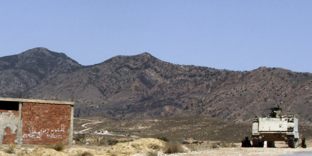 """In this photo taken on June 25, 2013, a Tunisian armored personnel carrier patrols near the Jebel Chaambi mountain. Writing on building at left reads: """"For Sale"""". Gunmen ambushed a Tunisian army patrol Monday July 29, 2013 in a mountainous border region known as a militant stronghold, killing at least eight soldiers, the presidential spokesman said. (AP Photo/Paul Schemm)"""