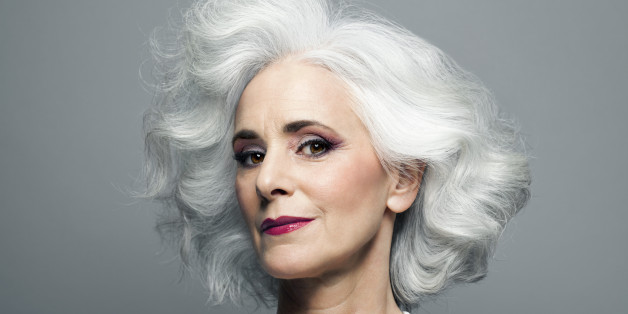 Mature woman with medium length, big, wavy, silvery, grey hair in front of grey background wearing make up red lip stick, portrait.