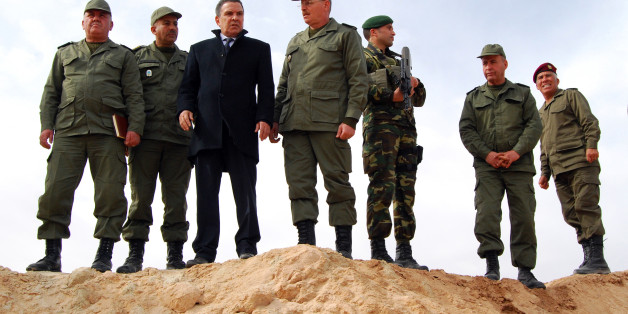 Tunisian Defense minister Farhat Horchani, third left, with Chief of Staff of the Army Ismael Fathalli, center, attend a presentation of the anti-jihadi fence, in near Ben Guerdane, eastern Tunisia, close to the border with Libya, Saturday, Feb. 6, 2016. Tunisia's defense minister has visited an anti-jihadi fence that's being built on the country's border with Libya to stop Islamist militants from entering Tunisian territory. Defense Minister Farhat Horchani inspected the first completed part of the 196-kilometer (122-mile) fence Saturday, which aims to counter the threat from jihadi militants and render the entire border impassable by vehicles. Horchani said the project came about with financial assistance from Germany and the U.S. (AP Photo/Benjamin Wiacek)