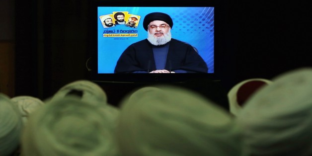 FILE- In this Tuesday, Feb. 16, 2016 file photo, Shiite and Sunni clerics listen to Hezbollah leader Sayyed Hassan Nasrallah as he speaks via a video link, during a ceremony to honer fallen Hezbollah leaders, in the southern suburbs of Beirut, Lebanon. A Saudi-led bloc of six Gulf Arab nations formally branded Hezbollah a terrorist organization on Wednesday, ramping up the pressure on the Lebanese militant group fighting on the side of President Bashar Assad in Syria. (AP Photo/Bilal Hussein, File)