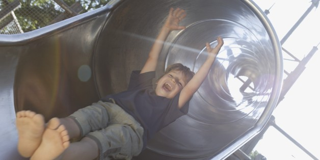 Boy sliding down slide at playground