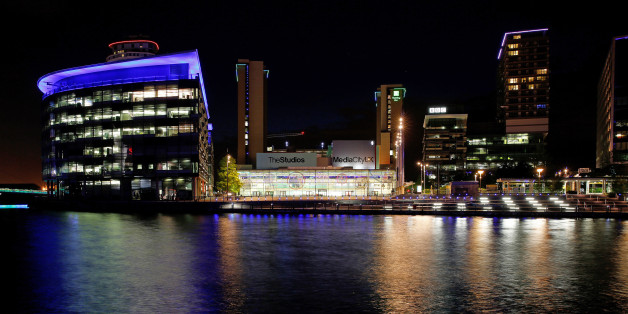 The lights of offices and restaurants are reflected in the water at MediaCityUK in Salford Quays, Manchester, U.K., on Friday, May, 29, 2015. Since the Conservatives won the general election, U.K. Chancellor of the Exchequer George Osborne announced sweeping devolution for Manchester and other English cities. Photographer: Paul Thomas/Bloomberg via Getty Images