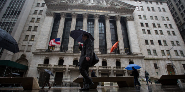 Pedestrians carry umbrellas while walking past the New York Stock Exchange (NYSE) in New York, U.S., on Wednesday, Feb. 24, 2016. U.S. stocks rose, benchmark indexes climbing back from declines of more than 1 percent as crude stabilized near $32 a barrel in New York. Photographer: Michael Nagle/Bloomberg via Getty Images