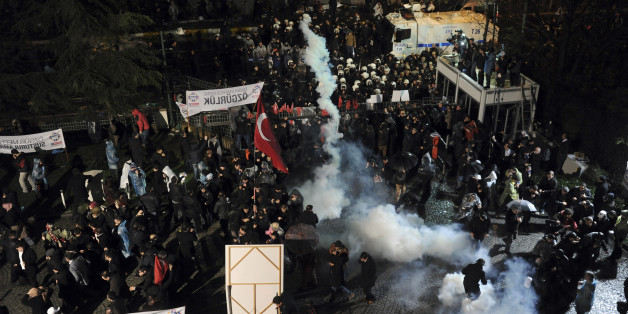 Riot police use tear gas against people gathered in support of Turkey's largest-circulation newspaper Zaman at its headquarters in Istanbul, Friday, March 4, 2016. The police raid came hours after a court placed it under the management of trustees on Friday. The move against the paper, which is linked to an opposition cleric, heightened concerns over deteriorating press freedoms in the country. (AP Photo)