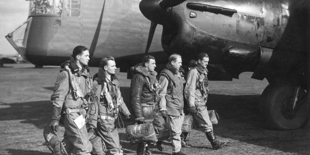 World War II British airforce bomber crew walking in front of aircraft.From left to right: Observer, Wireless Operator, Rear Gunner, Second Pilot, Pilot Captain.