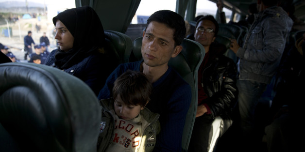 An Afghan family sit inside a bus as they leave with others the northern Greek border station of Idomeni, on Tuesday, Feb. 23, 2016. In an early morning operation, police at the Greek-Macedonian border ordered mostly Afghan migrants onto buses bound for Athens.  The migrants are being taken to an army-built camp near Athens that was set up last week, following European Union pressure on Athens to complete screening and temporary housing facilities. (AP Photo/Petros Giannakouris)