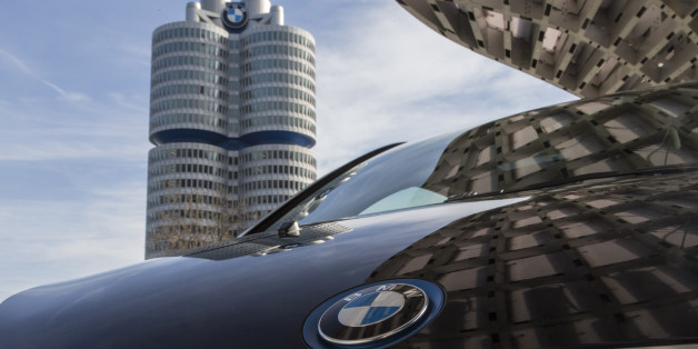 A BMW i3 plug-in automobile, produced by Bayerische Motoren Werke AG, sits outside the BMW World showroom as the automaker's headquarter towers stand beyond in Munich, Germany, on Tuesday, Jan. 26, 2016. BMW is at risk of losing its lead in the luxury car market this year to Mercedes-Benz after reporting the slowest sales growth since 2009 while its German arch-rival charged ahead with a fresher lineup and surging demand in China. Photographer: Martin Leissl/Bloomberg via Getty Images
