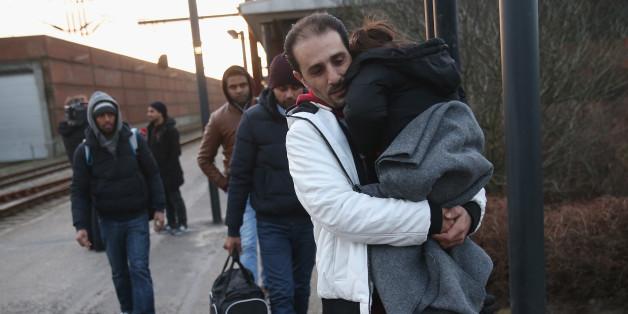 Während Einheimische starren, helfen Flüchtlinge einer jungen Frau nach einem Autounfall.