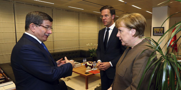 Turkey's Prime Minister Ahmet Davutoglu, left, listens to Germany's Chancellor Angela Merkel, right as Mark Rutte, centre, Prime Minister of Netherlands, looks on, during their meeting at Turkey's permanent delegation to the European Union, in Brussels, late Sunday, March 6, 2016. (Hakan Goktepe/Prime Minister's Press Service, Pool Photo via AP)