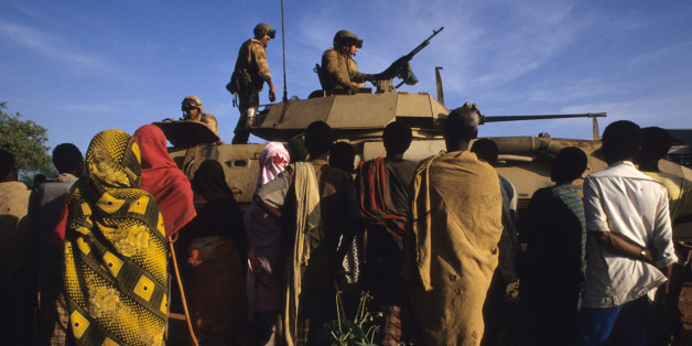 December 16, 1992. Baidoa, Somalia. US Marines atop a Bradley tank are seen delivering food aid to the famine stricken people of the Somali countryside. Late in 1992, troops from the United States and other nations attempted to restore political stability