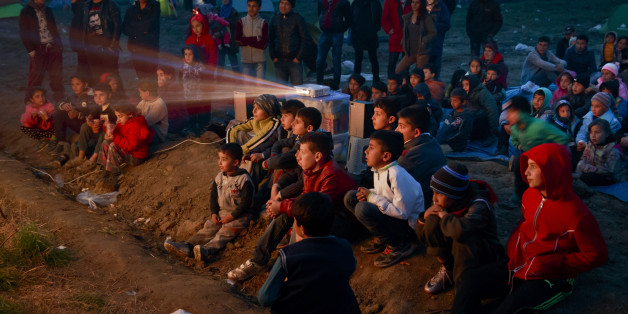 Children watch a cartoon movie in a field at the northern Greek border station of Idomeni, Saturday, March 5, 2016. The regional governor of the Greek region of Central Macedonia called on the Greek government Saturday to declare a state of emergency for the area surrounding the Idomeni border crossing saying that up to 14,000 people are trapped in Idomeni, while another 6,000-7,000 are being housed in refugee camps around the region, meaning the area was handling about 60 percent of the total number in the country. (AP Photo/Vadim Ghirda)