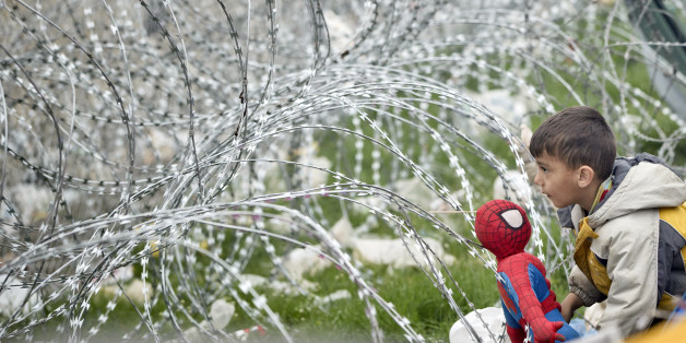 A boy plays with a Spiderman doll next to the razor wire around the fence between Greece and Macedonia at the northern Greek border station of Idomeni, Monday, March 7, 2016.  Greek police officials say Macedonian authorities have imposed further restrictions on refugees trying to cross the border, saying only those from cities they consider to be at war can enter as up to 14,000 people are trapped in Idomeni, while another 6,000-7,000 are being housed in refugee camps around the region.(AP Phot
