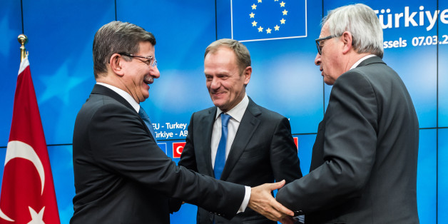 Turkish Prime Minister Ahmet Davutoglu, left, shakes hands with European Commission President Jean-Claude Juncker, right, and European Council President Donald Tusk, center, after a final media conference at an EU summit in Brussels on Tuesday, March 8, 2016. European Union leaders said early Tuesday they reached the outlines for a possible deal with Ankara to return thousands of migrants to Turkey and said they were confident a full agreement could be reached at a summit next week. (AP Photo/Geert Vanden Wijngaert)