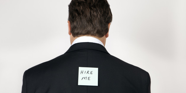 Man wearing a suit with 'hire me' note on his back