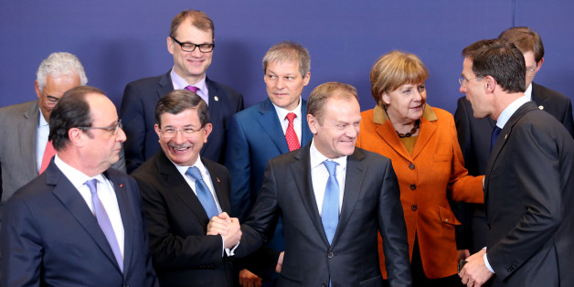 European Council President Donald Tusk, front center, shakes hands with Turkish Prime Minister Ahmet Davutoglu, front second left, during a group photo at an EU summit in Brussels on Monday, March 7, 2016. European Union leaders are holding a summit in Brussels on Monday with Turkey to discuss the current migration crisis. Other leaders left to right, Portuguese Prime Minister Antonio Costa, French President Francois Hollande, Finnish Prime Minister Juha Sipila, Romanian Prime Minister Dacian Ciolos, German Chancellor Angela Merkel, Dutch Prime Minister Mark Rutte and Slovenian Prime Minister Miro Cerar. (AP Photo/Francois Walshaerts)