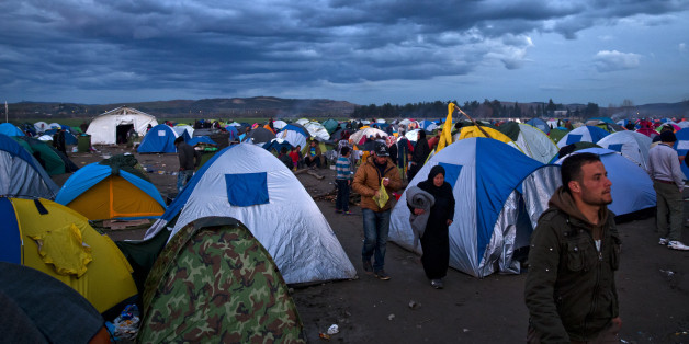 Migrants stand next to tents during rainfall at the northern Greek border station of Idomeni, Friday, March 4, 2016. More than 10,000 mostly Syrian and Iraqi refugees were stuck at the country's Idomeni border as Greek officials said that nearly 32,000 migrants were stranded in the country after drastically reduce of number of transiting migrants. (AP Photo/Vadim Ghirda)