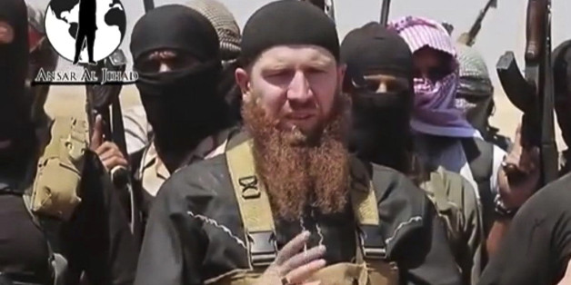 This image made from undated video posted during the weekend of June 28, 2014 on a social media account frequently used for communications by the Islamic State of Iraq and the Levant (ISIL), which has been verified and is consistent with other AP reporting, shows Omar al-Shishani standing next to the group's spokesman among a group of fighters as they declare the elimination of the border between Iraq and Syria. Al-Shishani, one of hundreds of Chechens who have been among the toughest jihadi fig