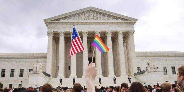 FILE - In this June 26, 2015 file photo, a man holds a U.S. and a rainbow flag outside the Supreme Court in Washington after the court legalized gay marriage nationwide. (AP Photo/Jacquelyn Martin, File)