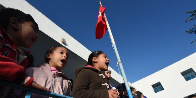 Tunisian schoolchildren sing their national anthem in a primary school in the Tunis suburb of Ariana on March 9, 2016 after having observed a minute of silence for the victims of attacks blamed on the Islamic State group that left dozens dead.