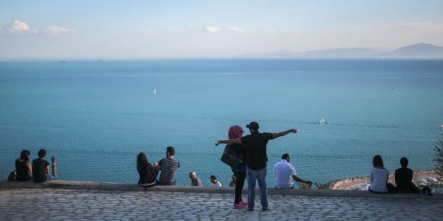 Couples observe a panoramic view of the Gulf of Tunis from the touristic village of Sidi Bou Said, some 20 kilometers outside of Tunis, Tunisia, Tuesday, Oct. 27, 2015. (AP Photo/Mosa'ab Elshamy)
