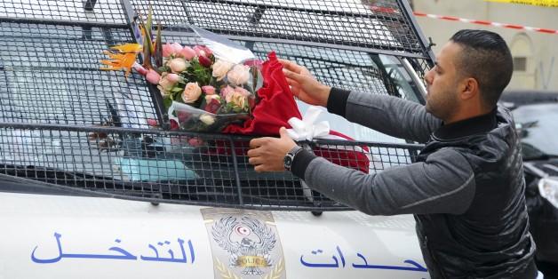 Le 25 novembre 2015, un homme place des fleurs sur un véhicule de police, à proximité des lieux de l'attentat ayant visé la garde présidentielle, 13 personnes.