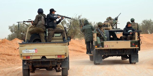 Members of the Tunisian military patrol a road near the Libyan border on March 10, 2016 in Bouhamed, 40 km from the town of Ben Guerdane, as they continue hunting jihadists in the area.  A nighttime curfew and tight security remain in place in Tunisia's Ben Guerdane area after clashes with jihadists that left dozens dead. / AFP / FATHI NASRI        (Photo credit should read FATHI NASRI/AFP/Getty Images)