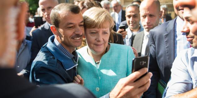 Bundeskanzlerin Angela Merkel (CDU) lässt sich im September 2015 nach dem Besuch der Erstaufnahmeeinrichtung für Asylbewerber der Arbeiterwohlfahrt (AWO) in Berlin-Spandau für ein Selfie zusammen mit einem Flüchtling aus dem Irak fotografieren (Archivbild)