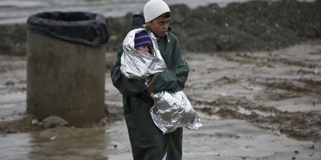 A migrant holds a baby covered in a thermal blanket at a makeshift camp at the northern Greek border station of Idomeni, Sunday March 13, 2016. Bad weather returned after a brief pause and conditions in the refugee camp on the Greek-Macedonian where about 14,000 people are stranded have further deteriorated, many of its residents struggling to cope with the many challenges posed by the heavy rain. (AP Photo/Visar Kryeziu)