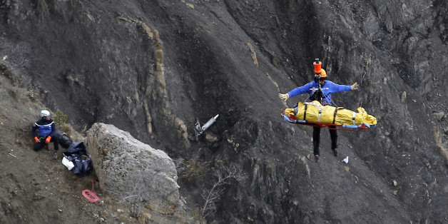 FOR USE AS DESIRED, YEAR END PHOTOS - FILE - A rescue worker is lifted into an helicopter at the crash site near Seyne-les-Alpes, France, Thursday, March 26, 2015. The co-pilot of a Germanwings jet barricaded himself in the cockpit and rammed the plane full speed into the French Alps, ignoring the captain's frantic pounding on the cockpit door and the screams of terror from passengers. In a split second, he killed all 150 people aboard the plane. (AP Photo/Laurent Cipriani, File)