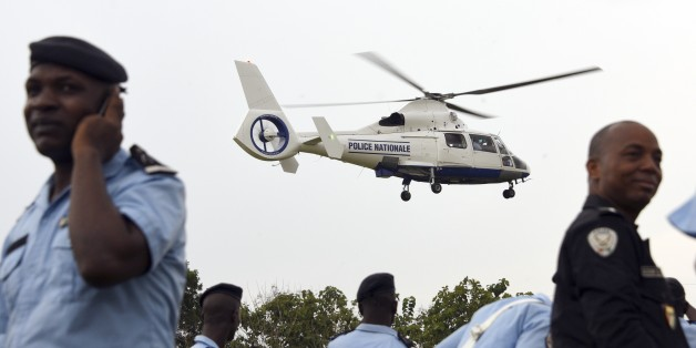 A helicopter handed over by the national council of security hovers over Ivorian policemen at the police academy in Abidjan on December 23, 2014 within the framework of modernising Ivory Coast's national police force. AFP PHOTO/SIA KAMBOU        (Photo credit should read SIA KAMBOU/AFP/Getty Images)