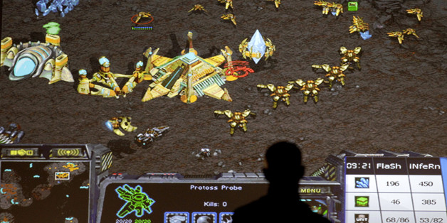 A man watches a StarCraft match between Young-Ho Lee, of South Korea, and Patrick Moeller, of Germany, at the 10th annual World Cyber Games in Los Angeles, Thursday, Sept. 30, 2010. (AP Photo/Jae C. Hong)