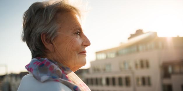 Senior woman standing on a roofgarden.