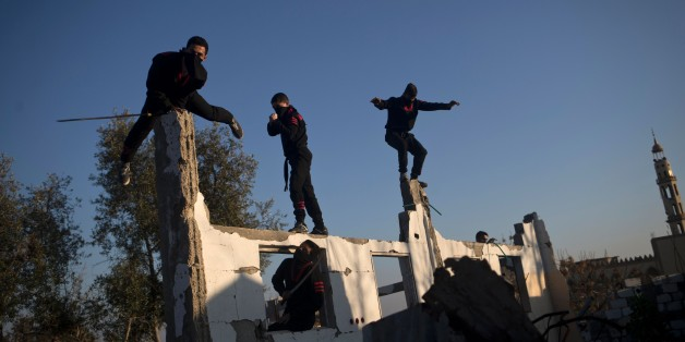 Palestinian youth, members of a Gazan martial art group, perform their ninja-like skills at ruins of a house, that was destroyed in the 2014 war between Israel and Hamas militants, in Beit Hanoun in the northern Gaza Strip, on February  11, 2016. / AFP / MOHAMMED ABED        (Photo credit should read MOHAMMED ABED/AFP/Getty Images)