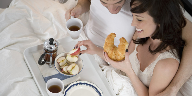 Portrait of happy young couple relaxing and having breakfast in bed