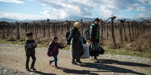 A migrant family crosses the Greek-Macedonian border near the town of Gevgelija, on February 14, 2016. 