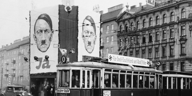 "Huge pictures of Reichsfuehrer Adolf Hitler and slogans reading ""For Greater Germany and Hitler"" on streetcars are shown in Vienna, April 10, 1938. (AP Photo)"