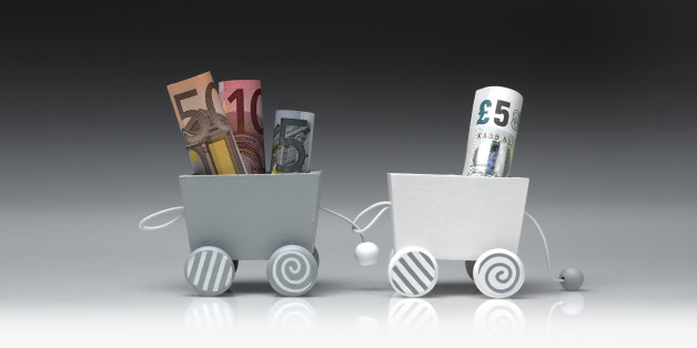 Detail of a toy train, consisting of two wooden wagons. The wagons are connected between them and they are shot on a gradient background. One wagon is pulling the other. The wagons are carrying euros and pounds in banknotes. The photograph was shot in a studio and its frame is horizontal.
