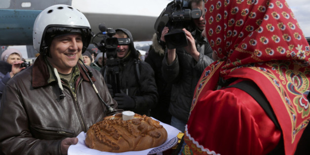 In this photo provided by the Russian Defense Ministry Press Service,  a Russian pilot who returned from Syria is welcomed with traditional bread-and-salt at an airbase near the Russian city Voronezh, Tuesday, March 15, 2016. Russian warplanes and troops stationed at Russia's air base in Syria started leaving for home on Tuesday after a partial pullout order from President Vladimir Putin the previous day, a step that raises hopes for progress at the newly reconvened U.N.-brokered peace talks in