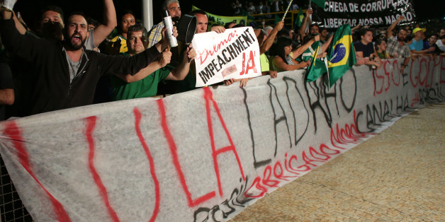 "Demonstrators shout slogans from behind a banner that reads in Portuguese: ""Lula thief,"" as they call for the impeachment of Brazil's President Dilma Rousseff and protest the naming of Lula da Silva as the president's new chief of staff, outside Planalto presidential palace in Brasilia, Brazil, Wednesday, March 16, 2016. Supporters say the move will help the president fight impeachment proceedings and critics blast it as a scheme to shield Lula from possible detention in corruption probes. (AP P"