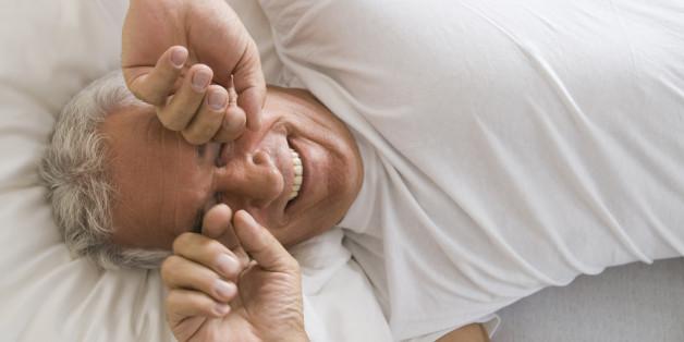 portrait of mature man awaking rubbing his eyes
