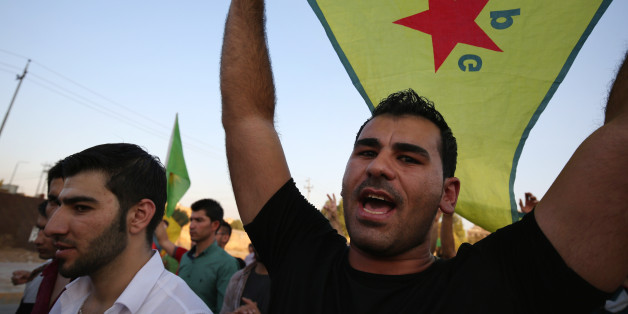 FILE - In this Saturday, July 25, 2015 file photo, a demonstrator waves the People's Protection Units flag, known as YPG, which is the main Kurdish fighting force in Syria, during a demonstration in Irbil, the Northern Kurdish region of Iraq. A spokesman for a powerful Syrian Kurdish political party said on Wednesday, March 16, 2016 that his faction is planning to declare a federal region in northern Syria, a model it hopes can be applied to the entire country. (AP Photo/Bram Janssen, File)