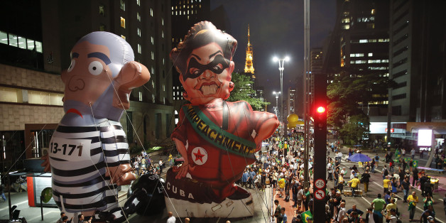 """Demonstrators march alongside large, inflatable dolls depicting Brazil's former President Luiz Inacio Lula da Silva in prison garb and current President Dilma Rousseff dressed as a thief, with a presidential sash that reads """"Impeachment,"""" during a protest calling for her impeachment and against the naming of her mentor, Silva, as her new chief of staff outside the Sao Paulo's Industries Federation in Sao Paulo, Brazil, Thursday, March 17, 2016. Rousseff's critics accuse her of a transparent mane"""