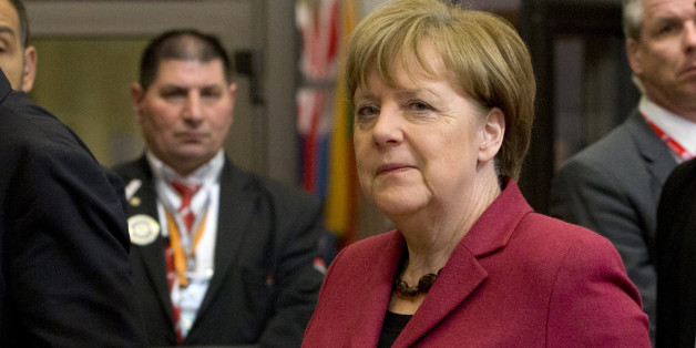 German Chancellor Angela Merkel, center, leaves an EU summit in Brussels on Friday, March 18, 2016. European Union leaders struggled to reach a deal Thursday that balanced their concerns about refugee law and Turkey's human rights record with their desperation to halt the migrant crisis. (AP Photo/Virginia Mayo)