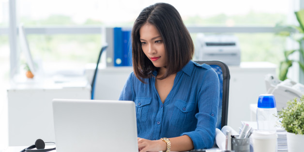 Concentrated businesswoman tying on laptop in office